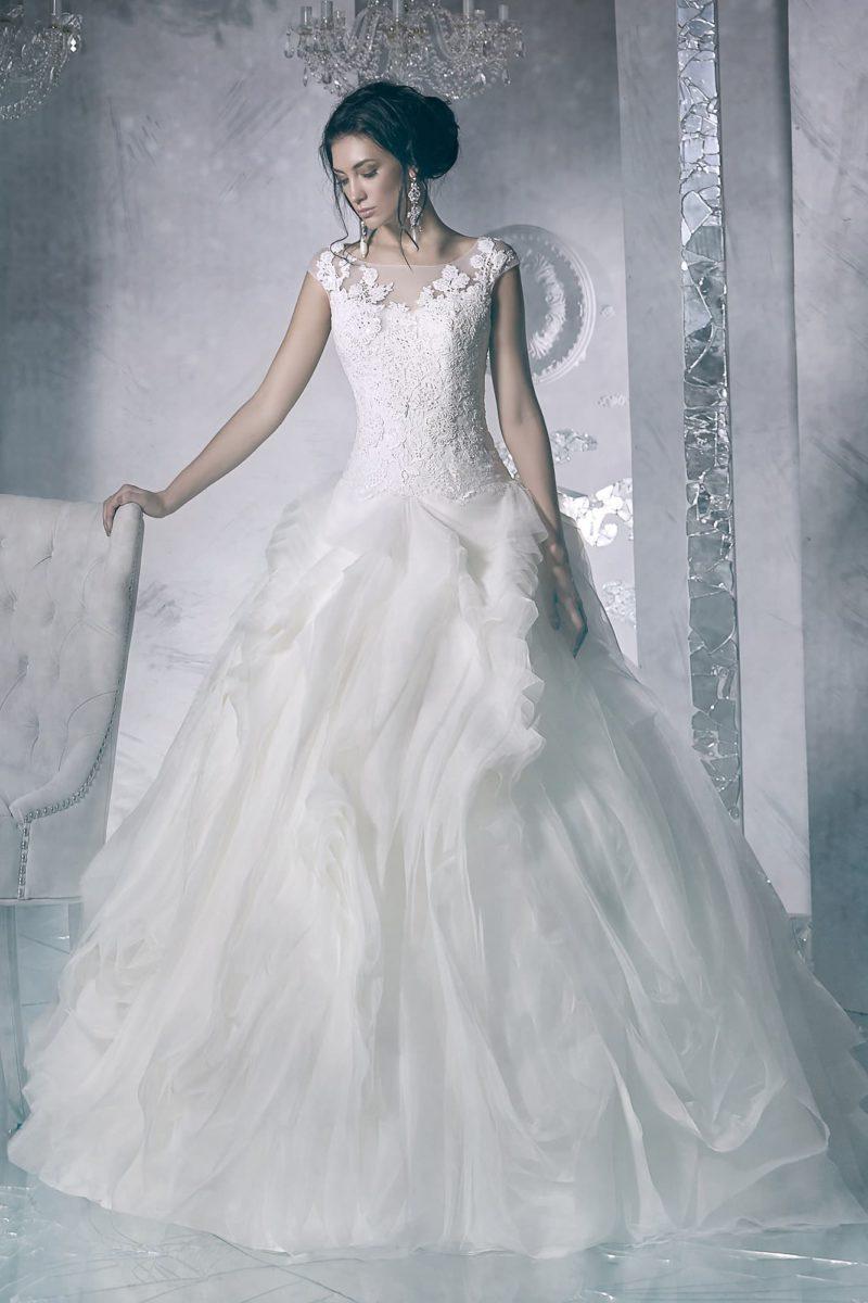 Роскошное свадебное платье с кружевной отделкой закрытого верха и многослойной юбкой.