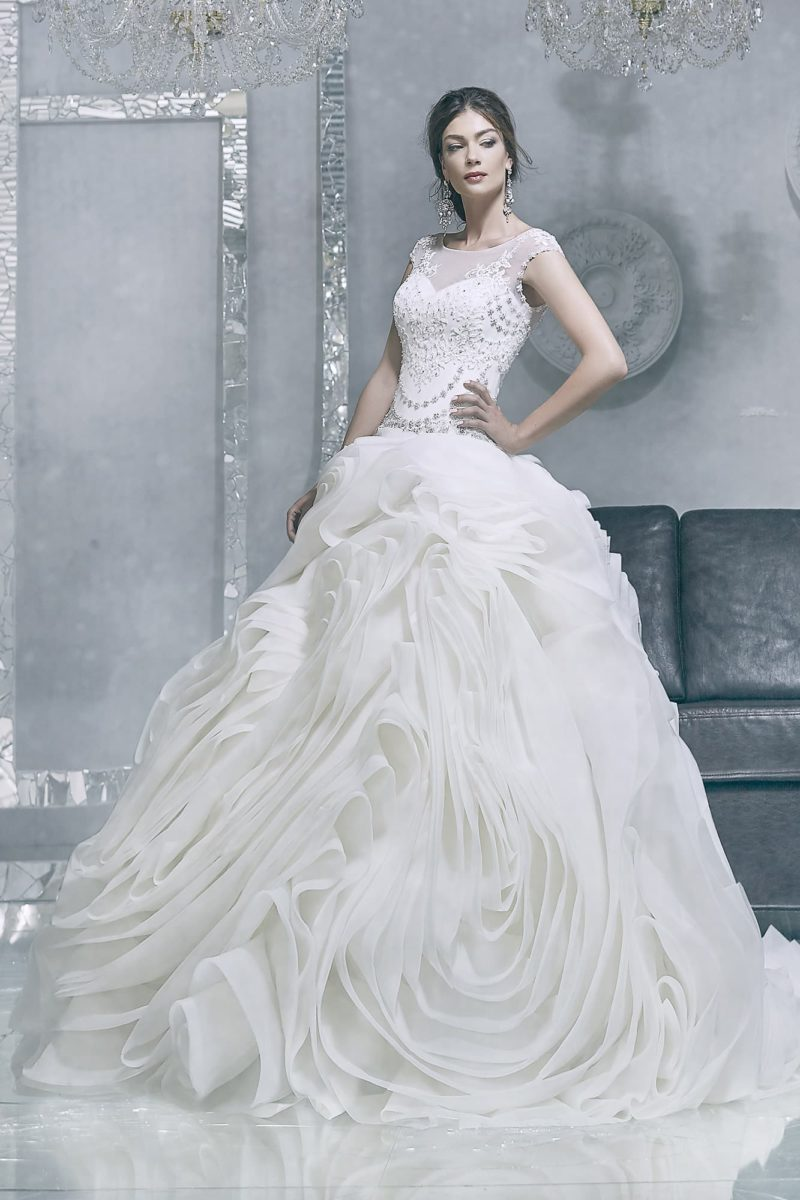 Драматичное свадебное платье с юбкой сложного кроя и облегающим лифом, расшитым бисером.