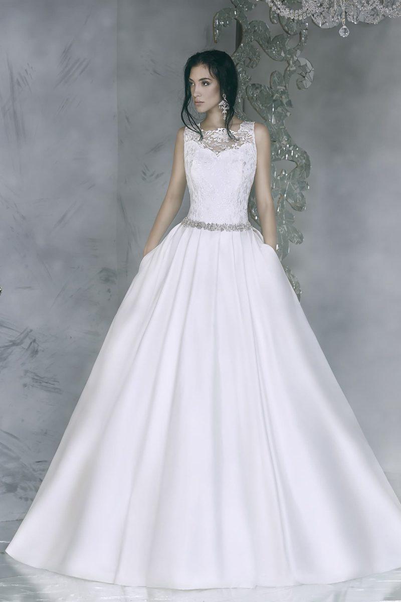 Сияющее свадебное платье с закрытым кружевным верхом и пышной юбкой из атласной ткани.