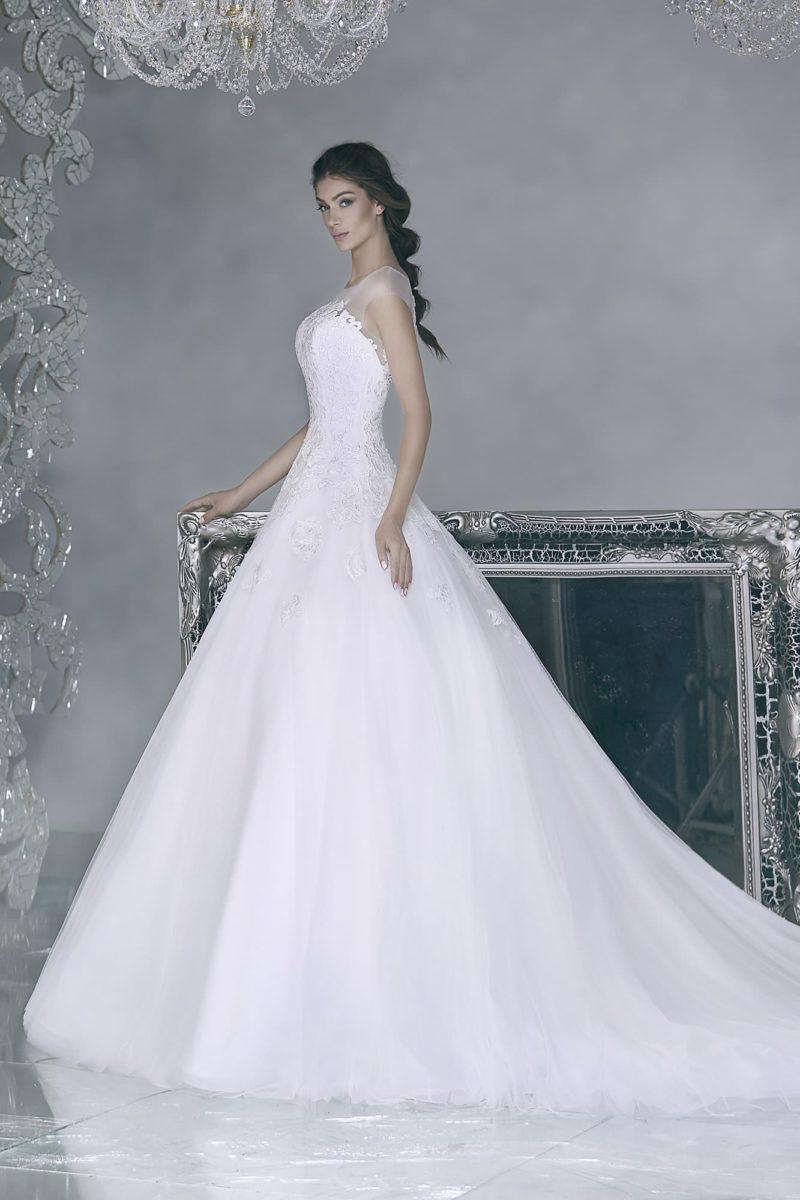 Элегантное свадебное платье с объемной юбкой со шлейфом и полупрозрачной отделкой верха.