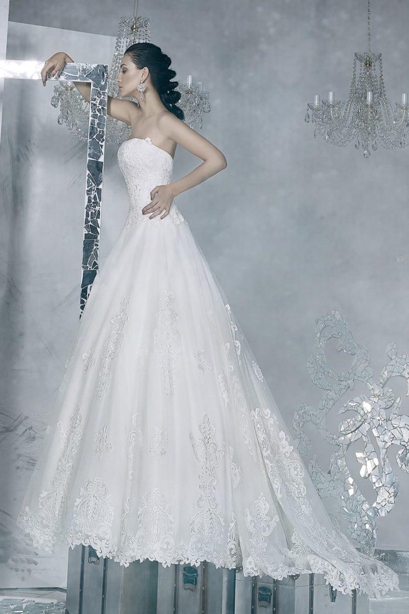 Открытое свадебное платье с лифом прямого кроя и многослойной юбкой со шлейфом и кружевным декором.