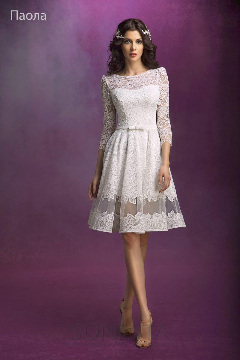 Короткое свадебное платье с пышной юбкой до колена, украшенной полупрозрачной вставкой.