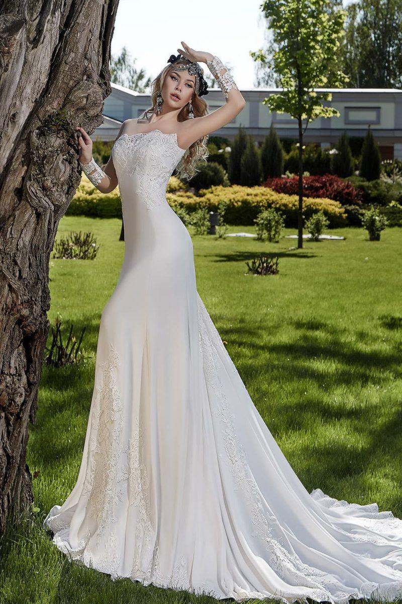 Прямое свадебное платье из утонченного шелка, украшенное кружевом по лифу и по низу подола.