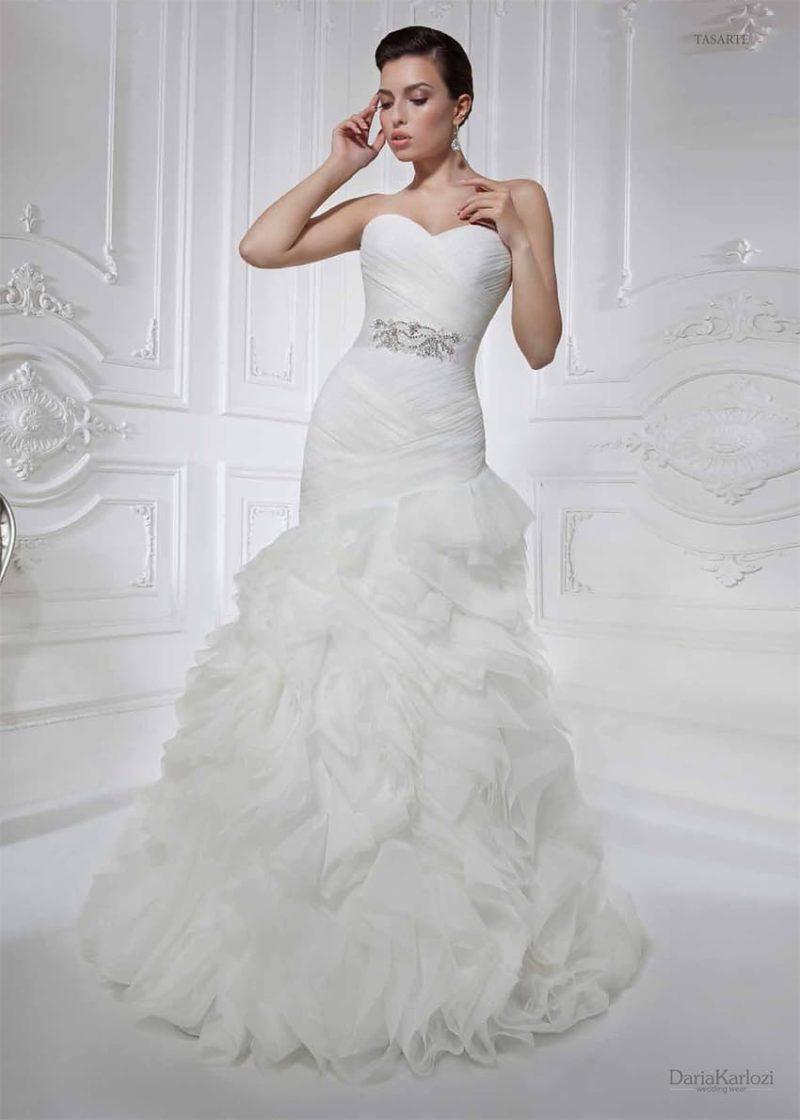 Притягательное свадебное платье с открытым корсетом, украшенным драпировками, и пышной юбкой.