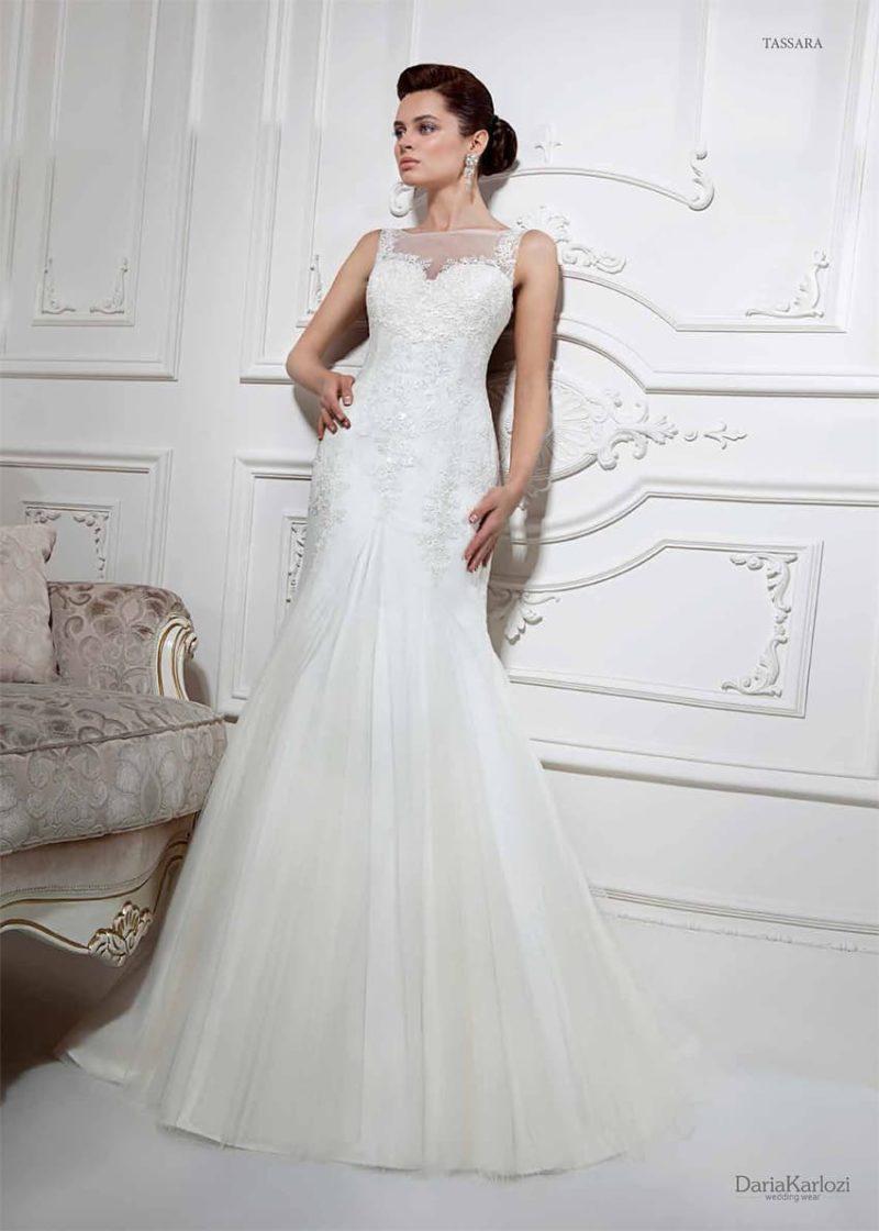 Изысканное свадебное платье облегающего кроя, покрытое кружевом и дополненное тонкой вставкой.