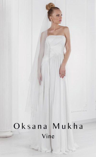 Прямое свадебное платье с открытым лифом и отделкой драпировками.