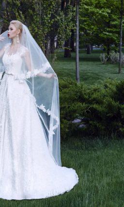 Торжественное свадебное платье из глянцевой ткани, с кружевной отделкой лифа и шлейфом.