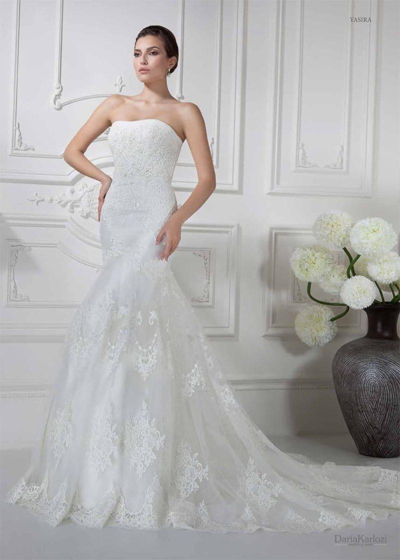 Изысканное свадебное платье с облегающим верхом и многослойным кружевным подолом.