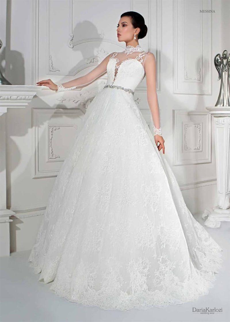 Пышное свадебное платье с глубоким декольте, укрытым тонкой тканью, и узким поясом.