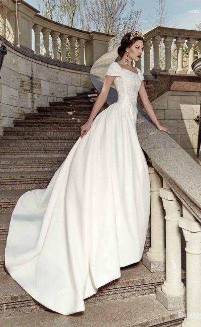 Пышное свадебное платье из фактурной атласной ткани, с изящным лифом и короткими рукавами.