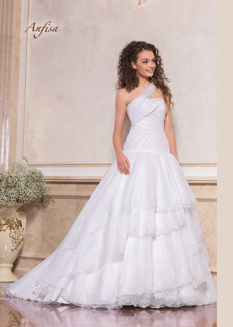 Пышное свадебное платье с асимметричным лифом и оборками по подолу.