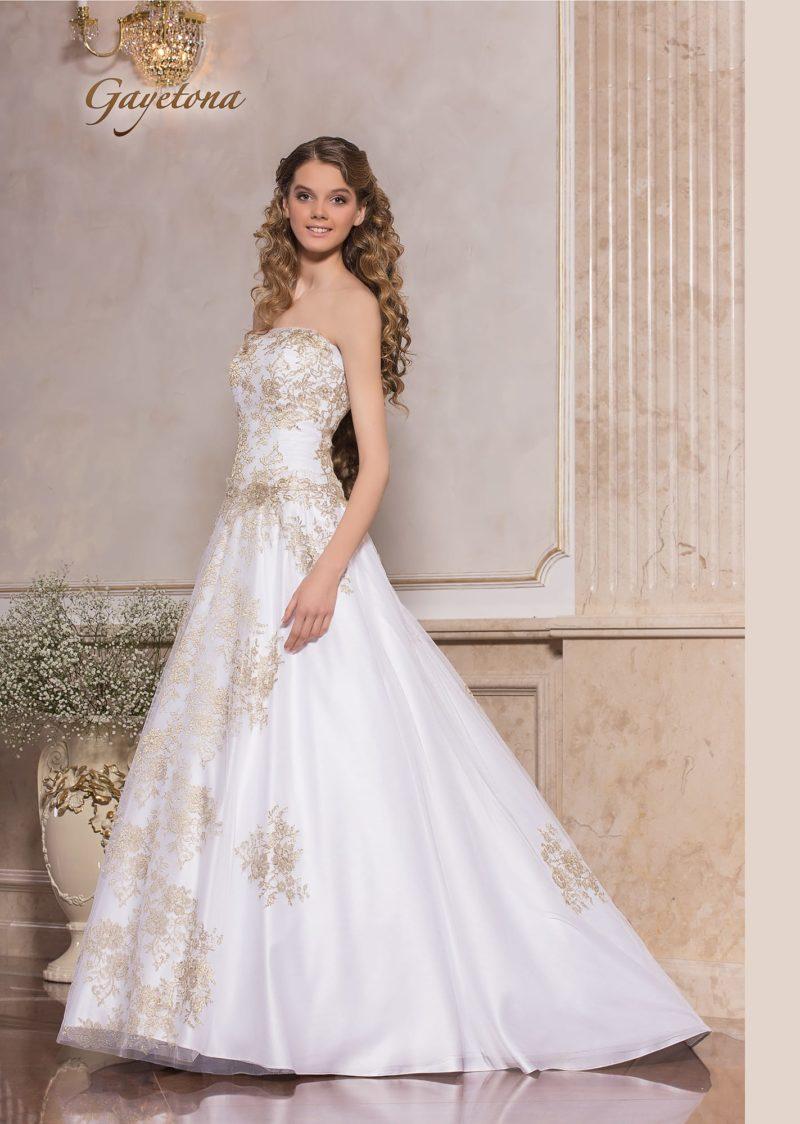 Романтичное свадебное платье А-силуэта с золотистым кружевным декором.