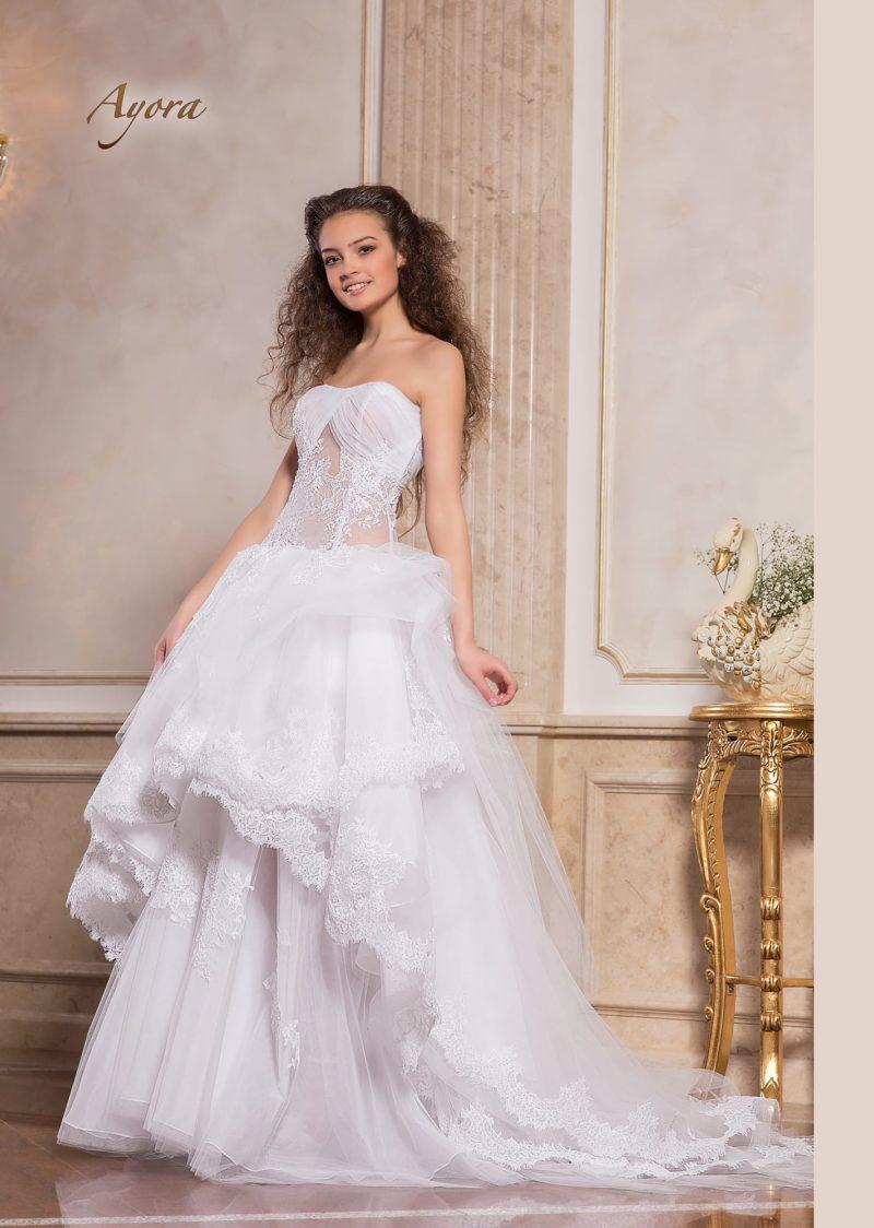 Свадебное платье с полупрозрачным верхом и пышной многослойной юбкой.