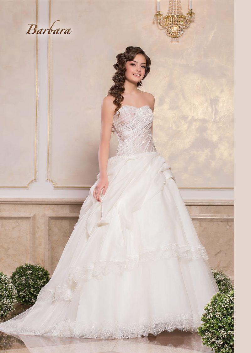 Пышное свадебное платье с лифом в форме сердца и отделкой драпировками.