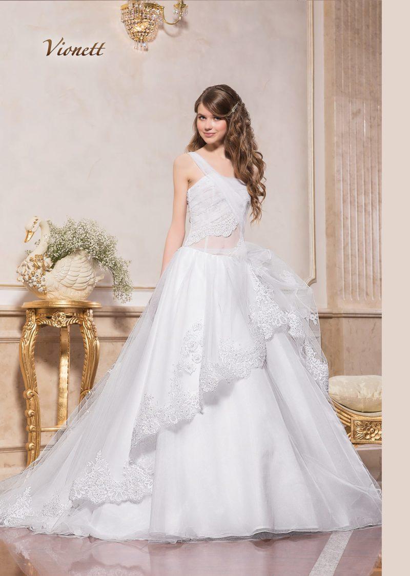 Пышное свадебное платье с кружевным декором юбки и полупрозрачным верхом.