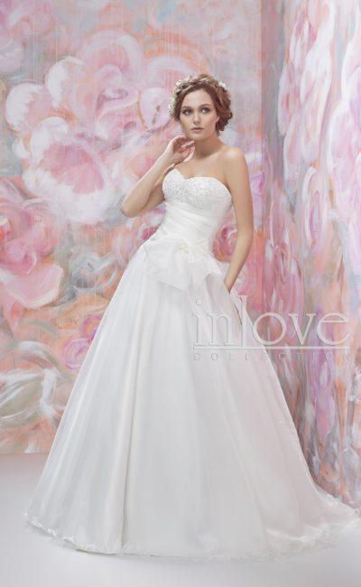 Пышное свадебное платье с вышивкой на открытом лифе и драпировками на талии.