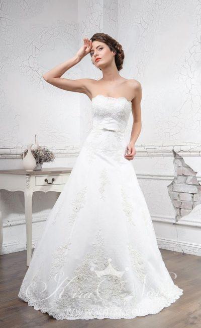 Свадебное платье А-силуэта с открытым лифом прямого кроя и кружевной отделкой.