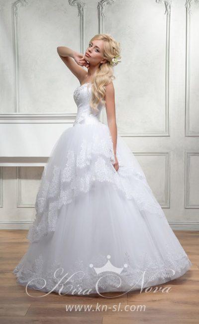 Пышное свадебное платье с многоярусной кружевной юбкой и открытым лифом с вышивкой.