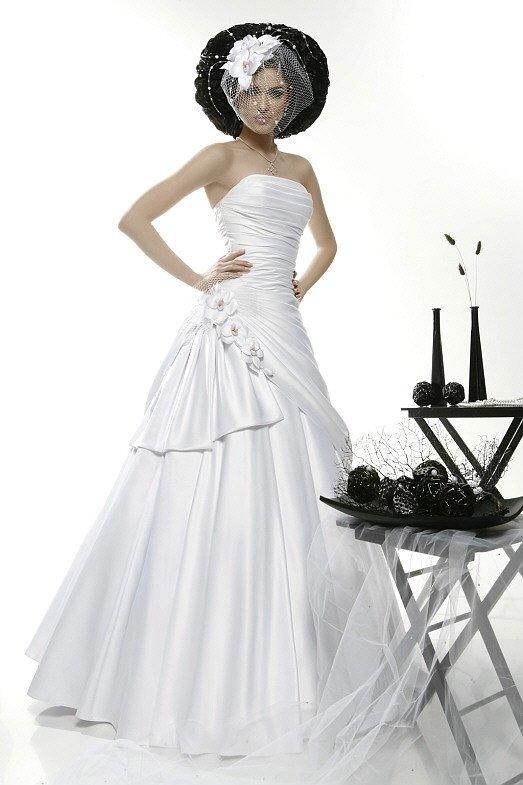 Свадебное платье из сияющего атласа, спускающегося от корсета драпировками.