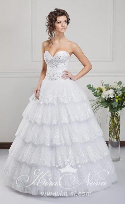 Роскошное свадебное платье с кружевными оборками на пышной юбке и открытым корсетом.