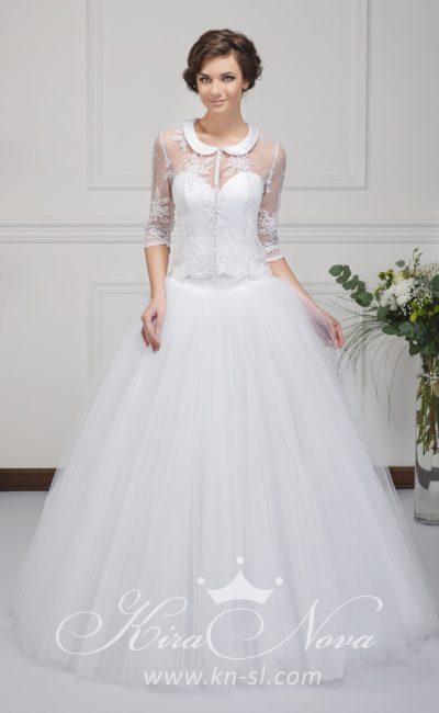 Необычное свадебное платье пышного кроя с округлым воротником и прозрачным рукавом.