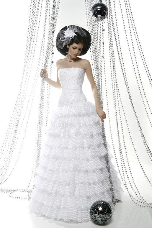 Свадебное платье с лифом прямого кроя и пышной юбкой с прозрачными оборками.