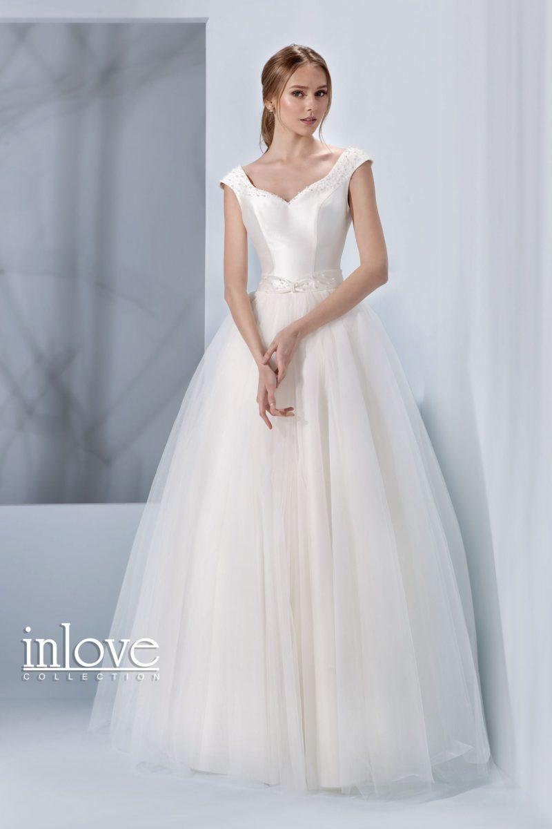 Впечатляющее свадебное платье с пышной юбкой и глубоким V-образным вырезом на спинке.
