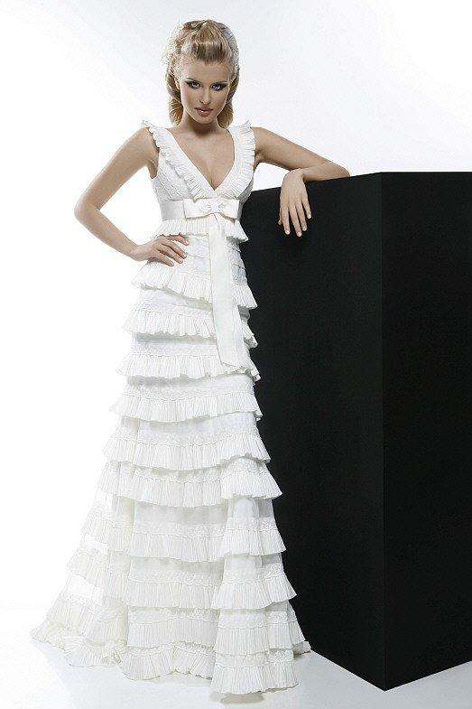 Свадебное платье с V-образным вырезом и множеством оборок на юбке А-силуэта.