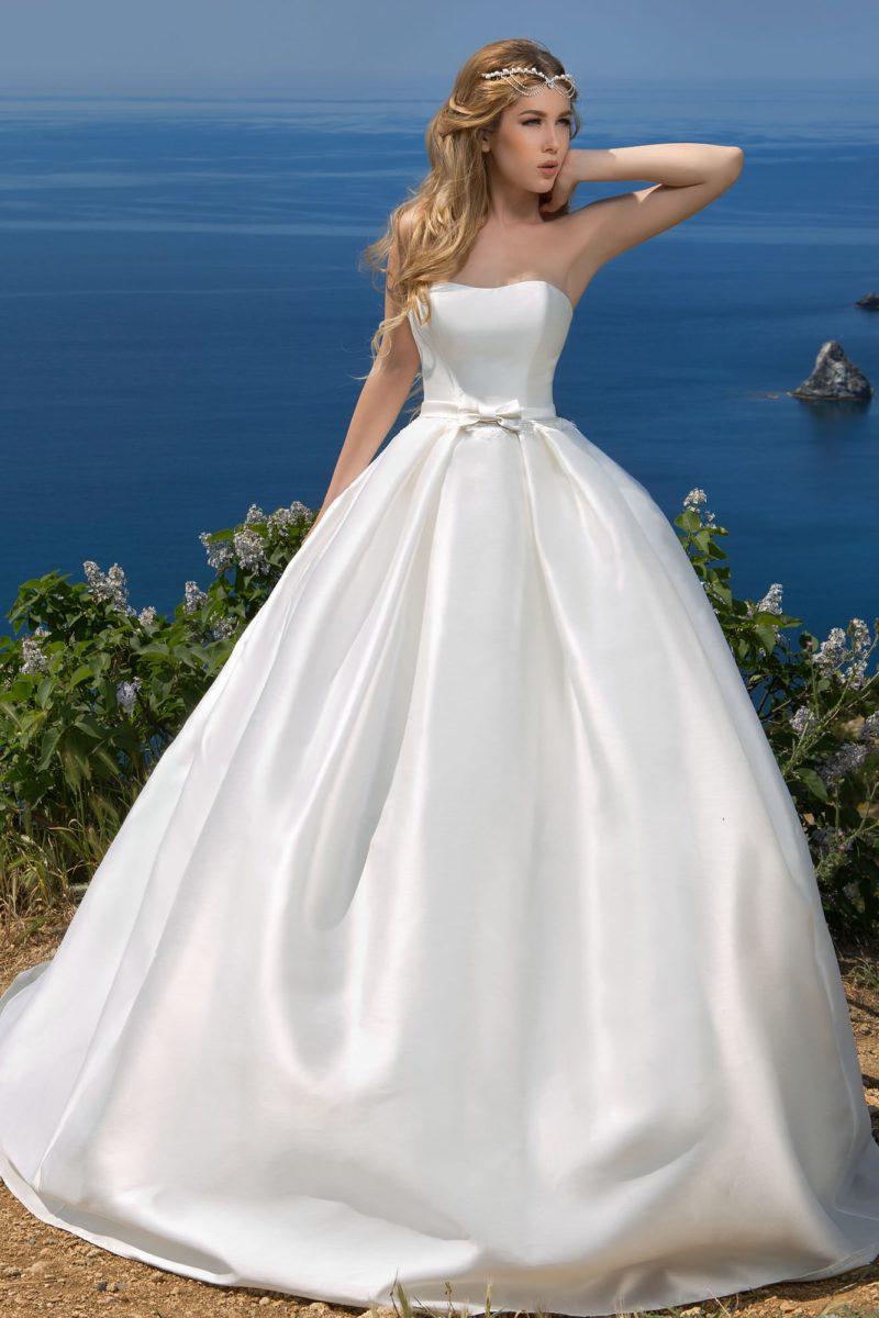 Атласное свадебное платье с узким поясом на талии и кружевным болеро над открытым лифом.