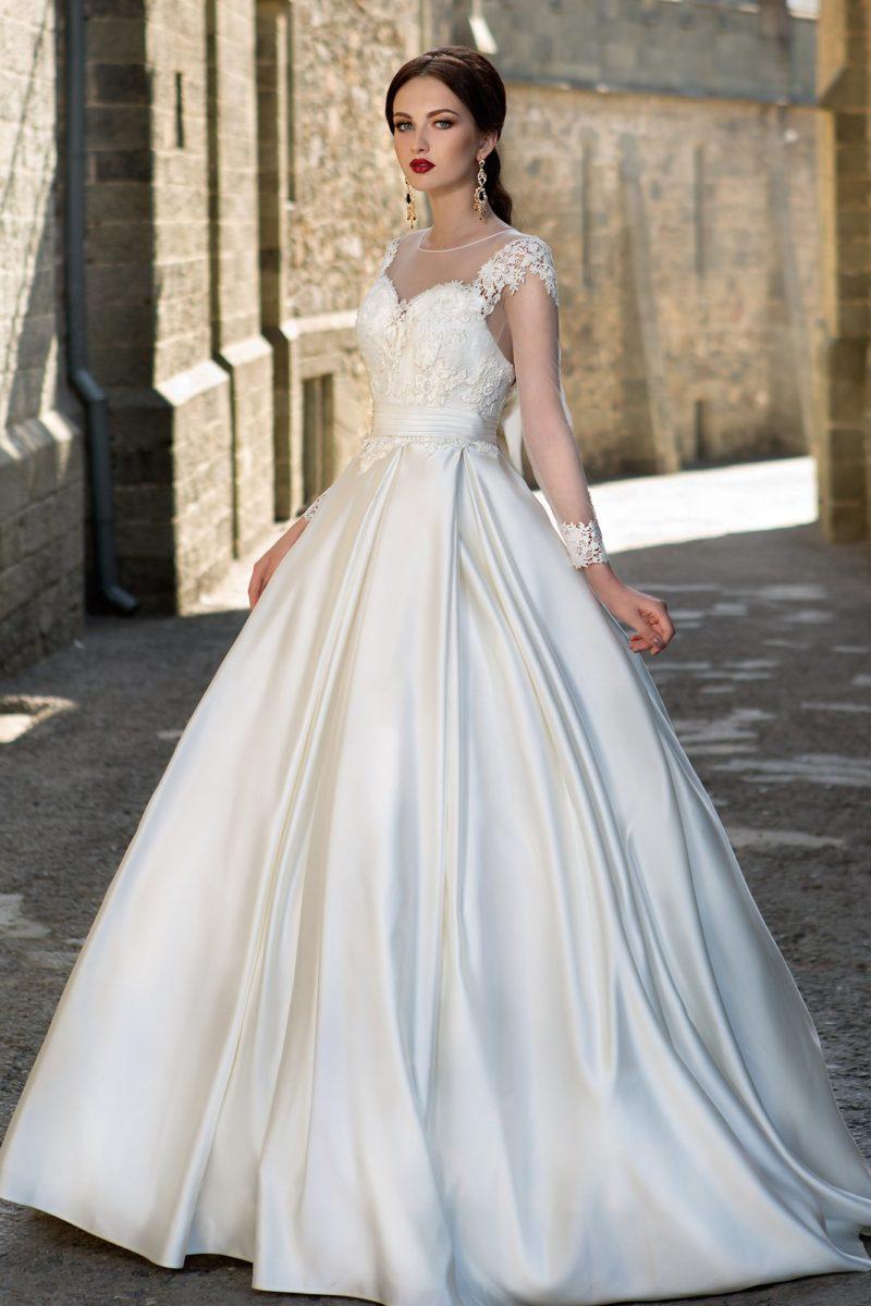 Атласное свадебное платье в торжественном стиле с лифом, оформленным прозрачной тканью.