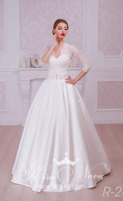 Атласное свадебное платье с широким поясом и небольшим V-образным вырезом, обрамленным кружевом.