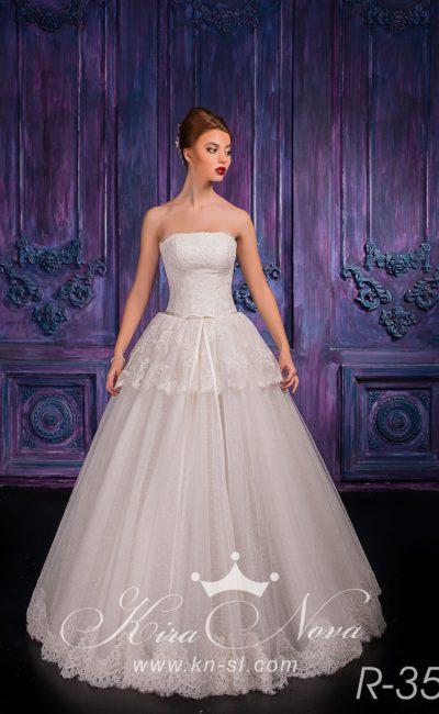 Пышное свадебное платье с кружевной баской на талии и узким поясом из атласной ткани.