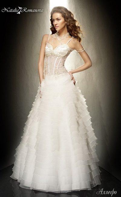 Свадебное платье с пышными оборками по подолу и открытым корсетом с атласным лифом.