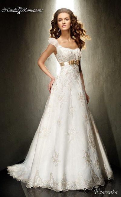 Свадебное платье «принцесса» с кружевной отделкой и золотистым атласным поясом с бантом.