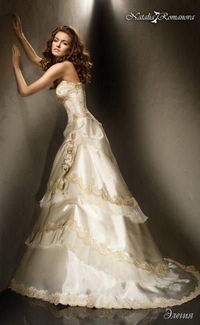 Сияющее свадебное платье золотистого оттенка с оборками по подолу и шлейфом сзади.