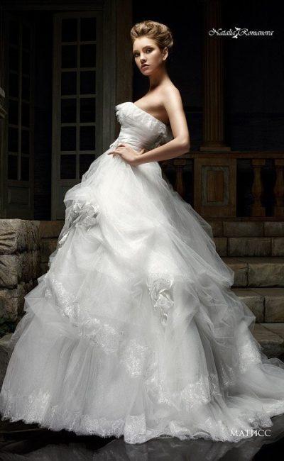 Великолепное свадебное платье с пышной юбкой, украшенной кружевом, и открытым лифом.
