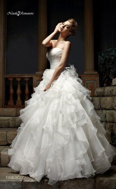 Великолепное свадебное платье с открытым декольте и пышным декором подола.