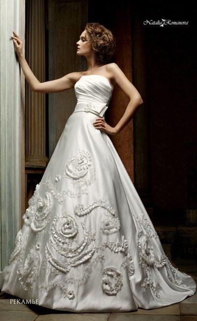 Атласное свадебное платье с лаконичным лифом и драматичной отделкой низа подола.