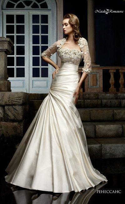 Атласное свадебное платье цвета слоновой кости, с декором из драпировок и коротким болеро.