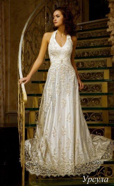 Свадебное платье с V-образным вырезом и атласной подкладкой под слоем тонкой кружевной отделки.
