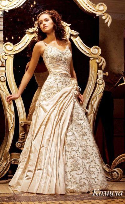 Торжественное свадебное платье из атласа кремового оттенка, украшенное тонкой кружевной тканью.