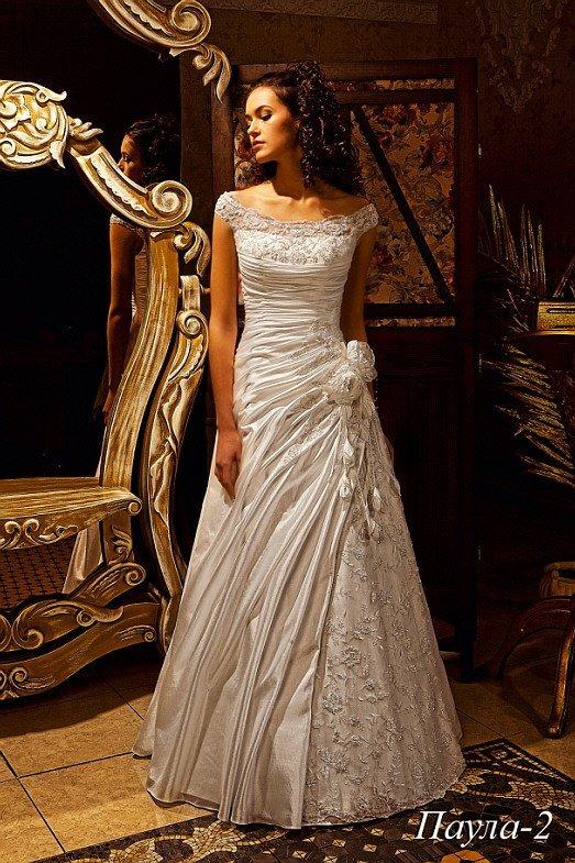 Свадебное платье с портретным декольте и отделкой из серебристой кружевной ткани и драпировок.