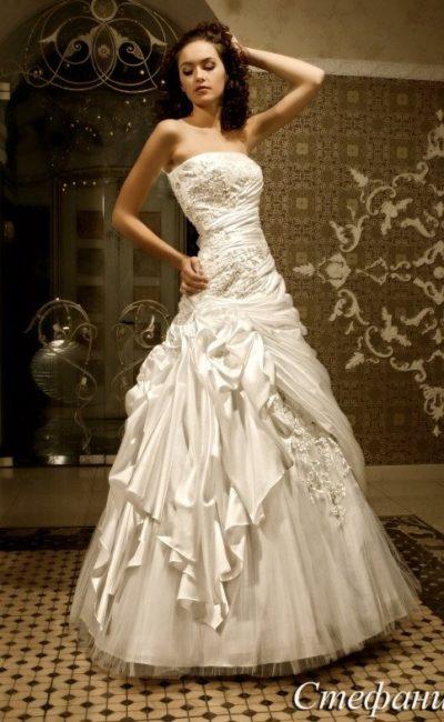 Великолепное свадебное платье с открытым лифом прямого кроя и сложными драпировками на юбке.
