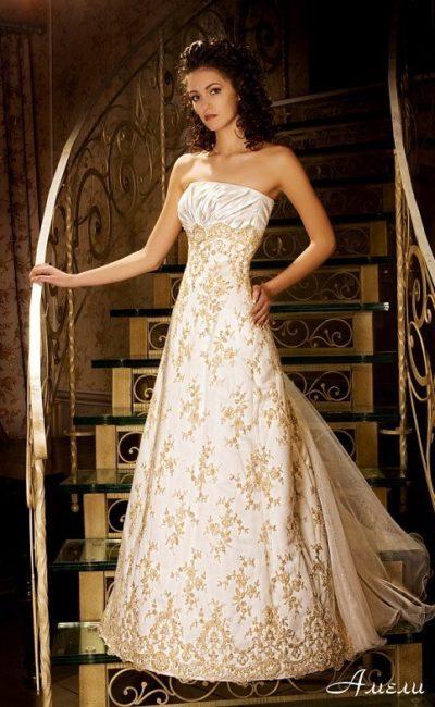 Стильное свадебное платье А-силуэта с открытым лифом и отделкой золотистой кружевной тканью.