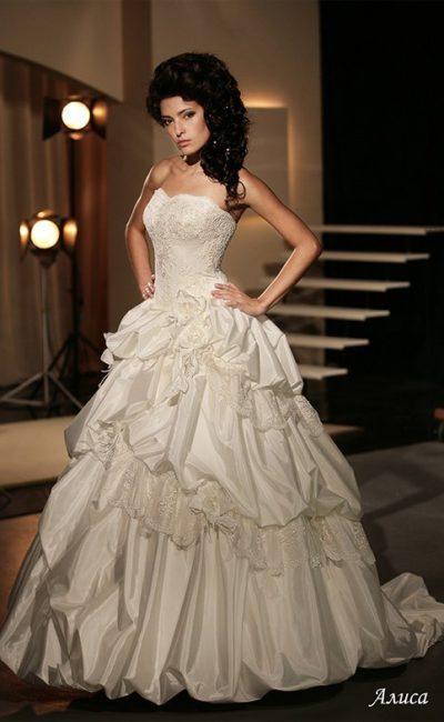 Кокетливое свадебное платье пышного кроя с оборками по подолу и открытым лифом.