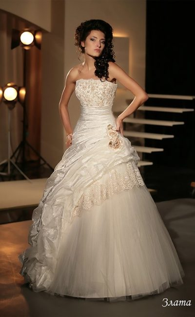 Свадебное платье с отделкой в пастельных тонах и романтичными оборками на юбке.
