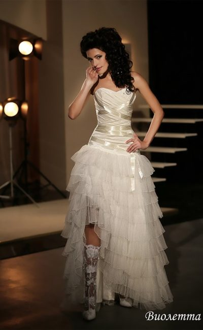 Кокетливое свадебное платье с открытым лифом и оборками по юбке с разрезом сбоку.