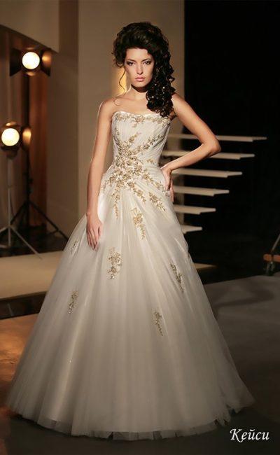 Открытое свадебное платье с отделкой золотистым кружевом и многослойной пышной юбкой.