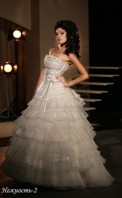 Великолепное свадебное платье пышного кроя с множеством полупрозрачных оборок.
