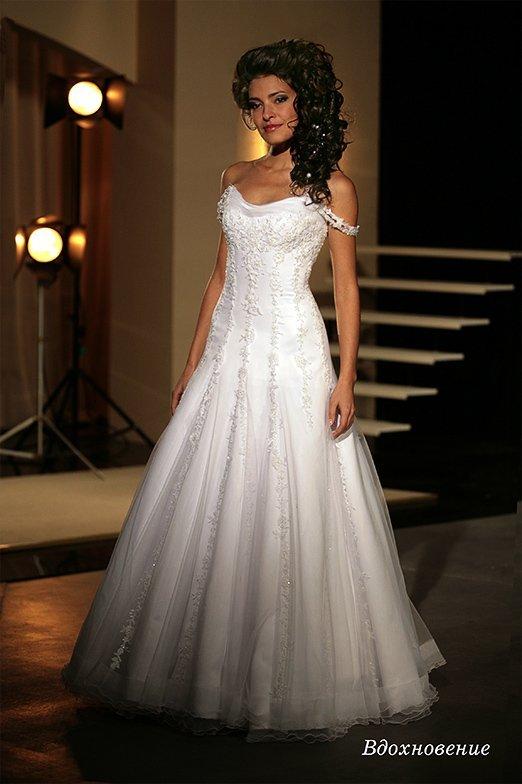 Нежное свадебное платье с бретелями на предплечьях и кружевной отделкой по всей длине.